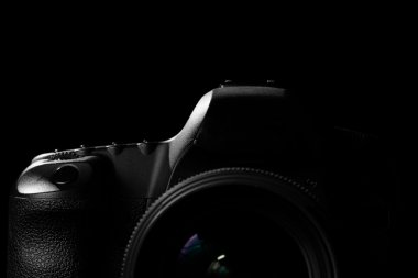 Image of a professional modern DSLR camera low key image - Modern DSLR camera  in a dark space. Top part of a camera is visible and the rest goes into the shadow stock vector