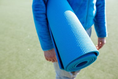 Woman walking with a yoga mat
