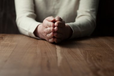 woman praying hands on wooden background
