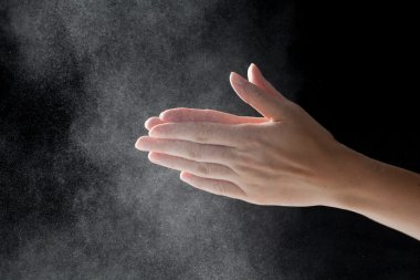 woman coating her hands in powder chalk magnesium