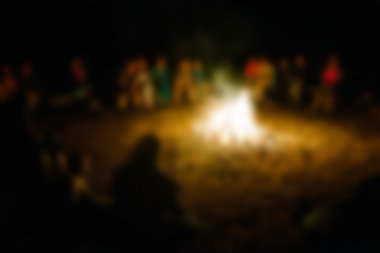 People sit at night round a bright bonfire. blurred