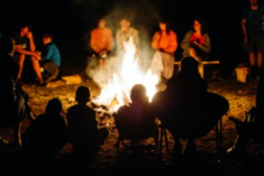 Blurred People sit at night round a bright bonfire