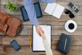 Dva podnikatelé potřesení rukou doma nad tabulku