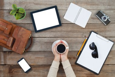 Hands holding a cup of coffe with digital tablet computer