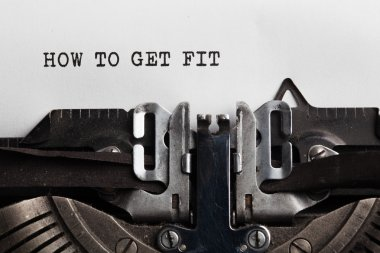 Get fit slogan on the sheet of a paper written by typewriter