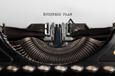 business plan written by a typewriter on a paper sheet. Space fo
