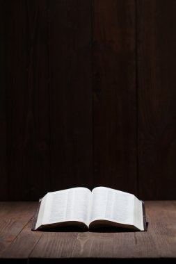 Image of a Holy Bible on wooden background in a dark space