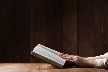 woman reading the bible in the darkness over wooden table