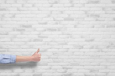 Hand with thumb up isolated on white brick wall background