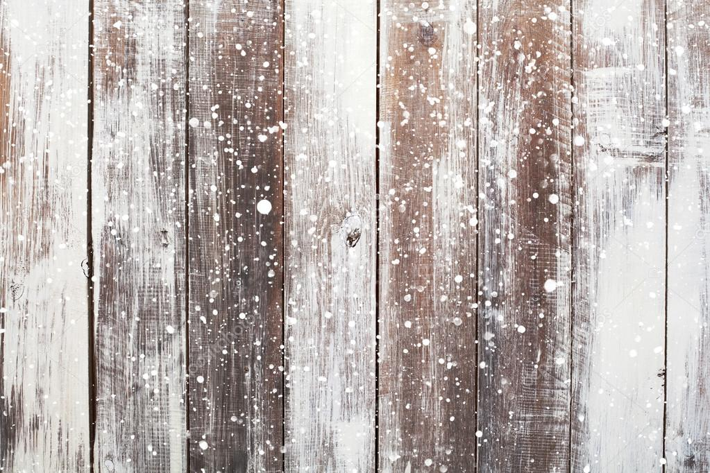 Christmas background with falling snow over wooden background