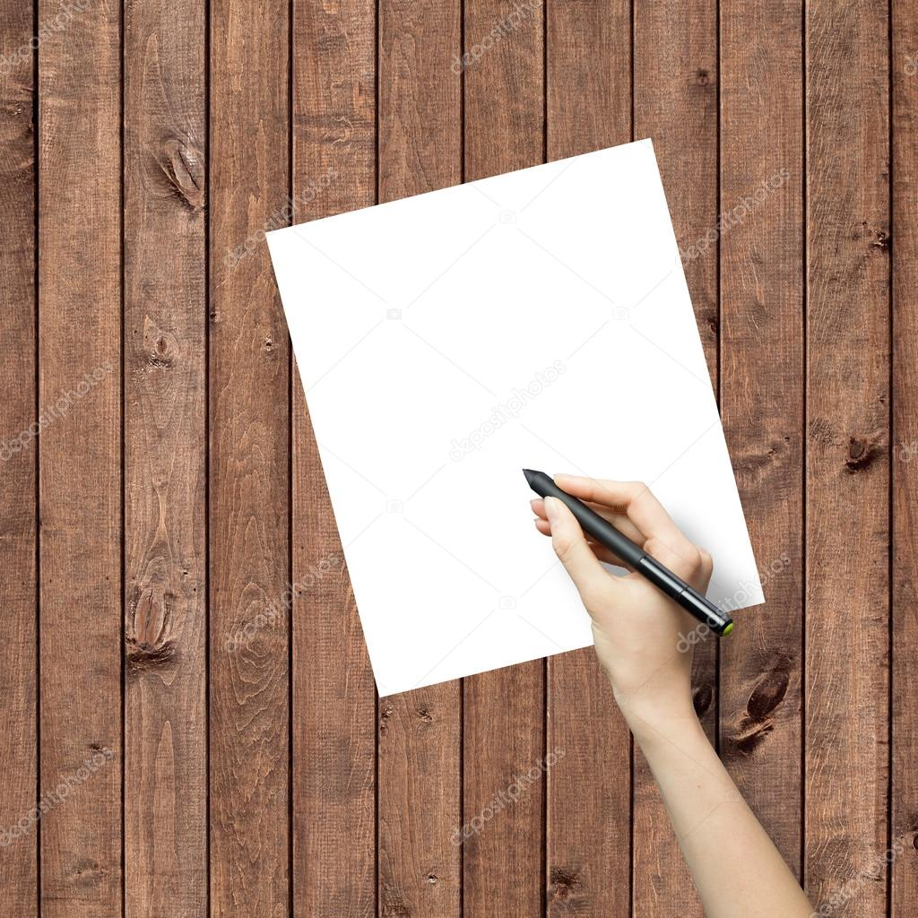 Hand drawing on white paper sheet with wooden texture background