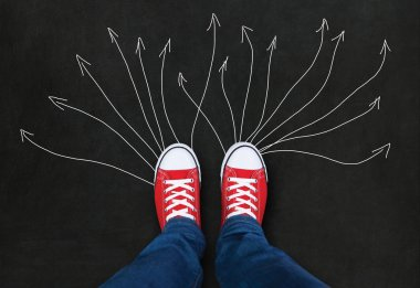 Feet wearing red shoes on black background with arrows. choice c