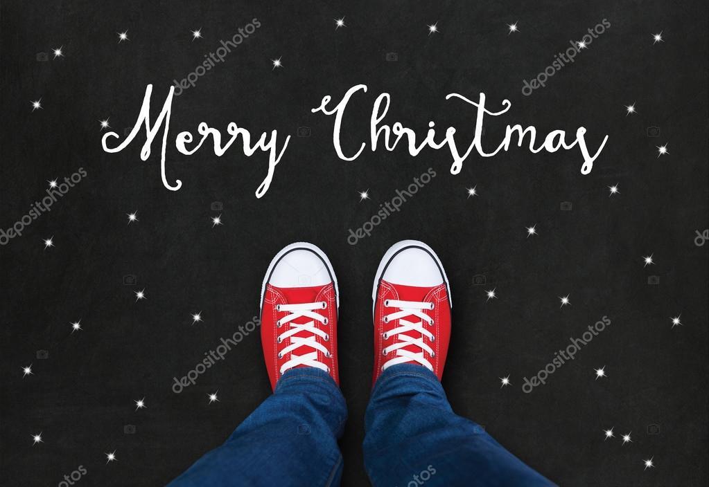 Füße in roten Schuhen auf schwarzem Hintergrund mit Merry Christmas ...