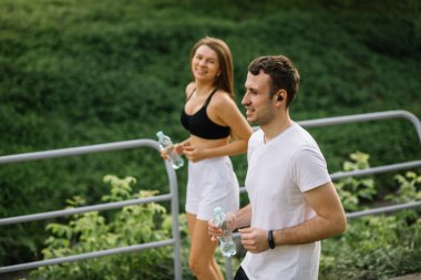 Young happy couple running in city park with botle of water in hands, joint sports, cheerfulness, city sport lifestyle