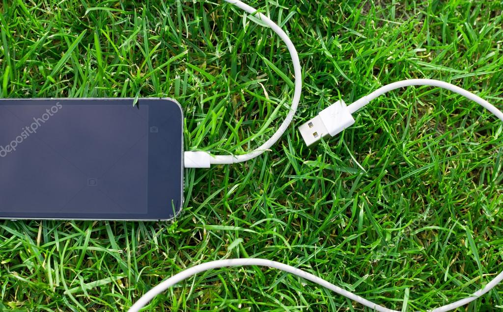 Phone detail with cable on grass