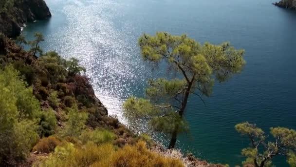 Güneş ışınları kıyı şeridi yakınlarındaki deniz suyunun yüzeyinde yatla oynar..