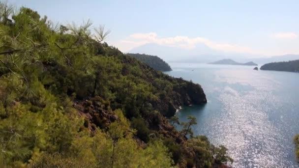 Güneş ışınları, deniz suyunun yüzeyinde, kıyı dağlarında yeşil ağaçlarla oynar..