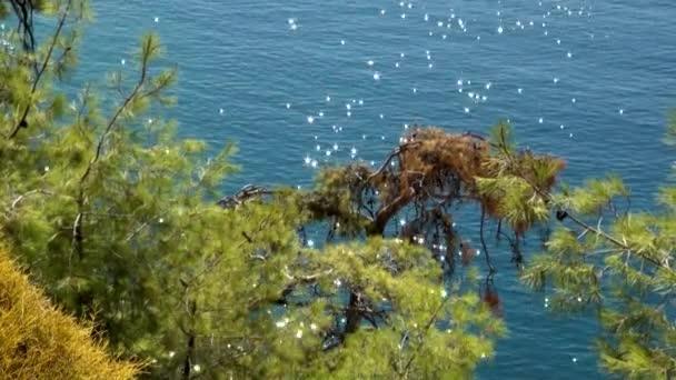 Güneş ışınları kıyı dağındaki deniz suyunun yüzeyinde parıldıyor ve parlıyor..