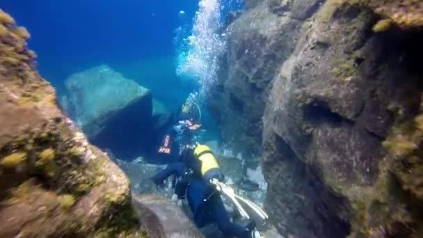 Divers near underwater rocks and crevices against the background of huge boulders in Atlantic ocean.