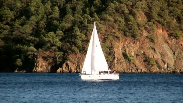 Beyaz yatlar gün ışığında yelken açar. Deniz ve dağların arka planında..