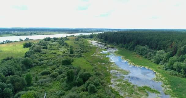 Letecký pohled panorama osady s domy a zahradami na řece obklopené zeleným polem s nádherným výhledem na krajinu kinematografické. Koncept podnebí venkovní příroda.