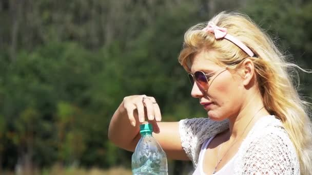 Beautiful girl with white hair sexy drinks water from a bottle. Slow motion.