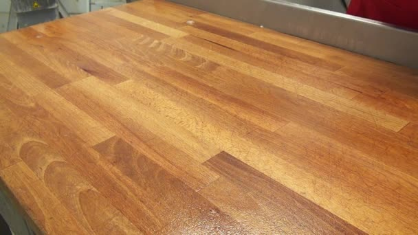 Clean surfaces and angles of a wooden table with a damp cloth.