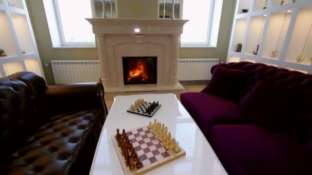 Sala panoramica con divani, caminetto e scacchi.