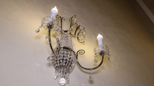 Lustr v podobě svíček na zdi.
