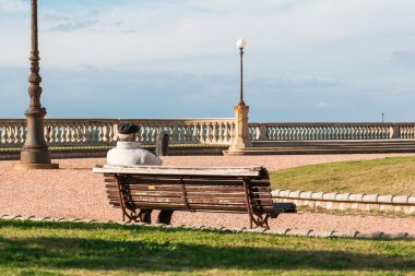 old lonely man sitting on public bench, waterside Solitude