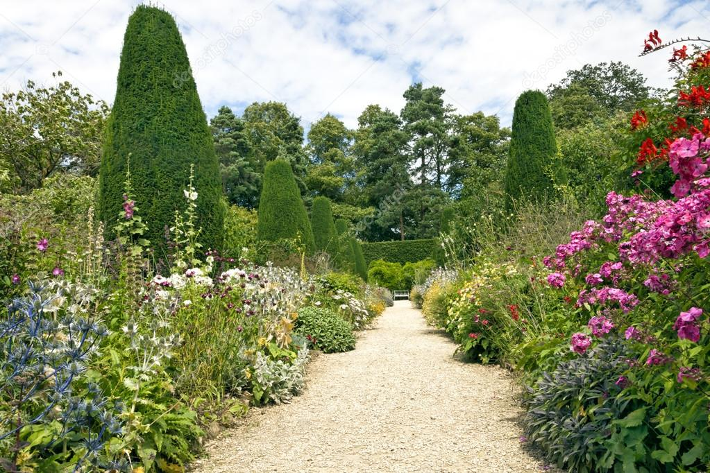Stone pathway leading to a white bench, with cottage colourful flowers in bloom on both sides, shaped conifers, shrubs and tall trees in an English garden on a sunny summer day