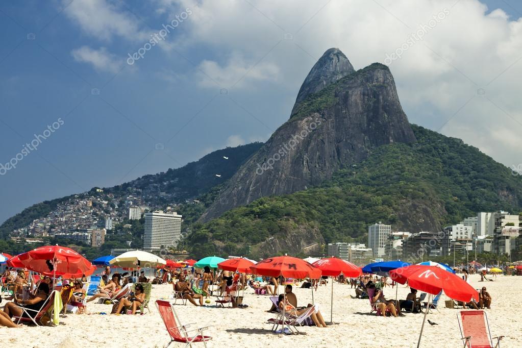 People Are Sunbathing Relaxing Under Beach Umbrellas On Ipanema In Rio De Janeiro