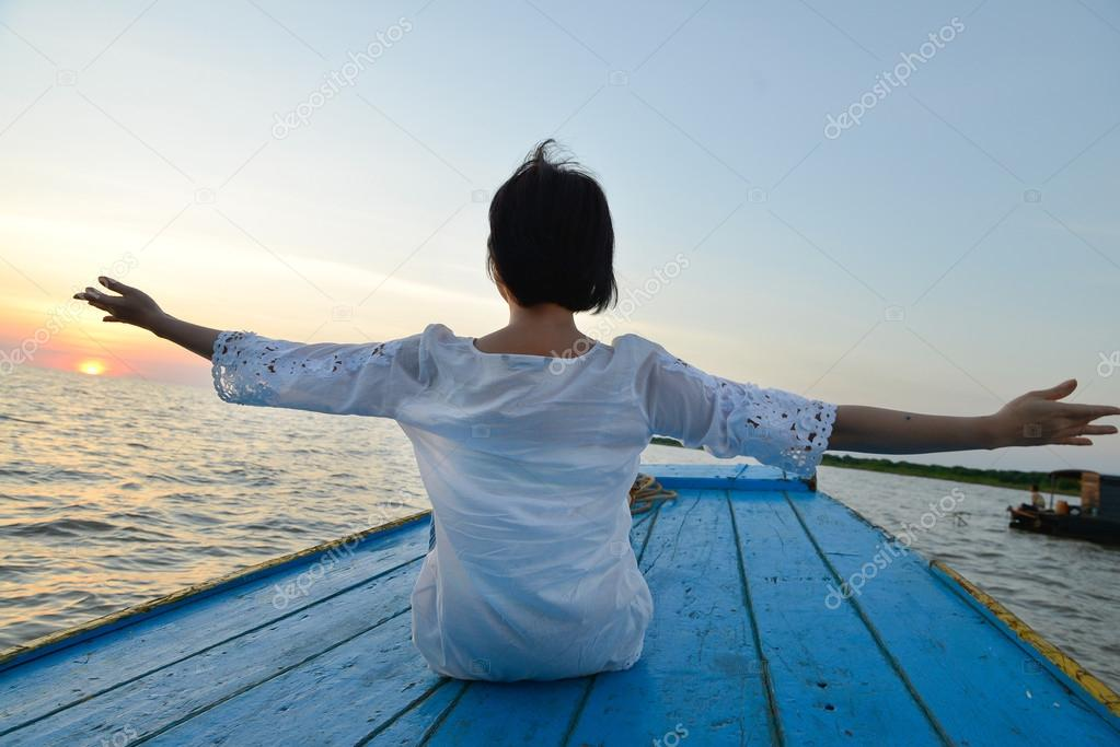 Woman doing yoga by wood boat
