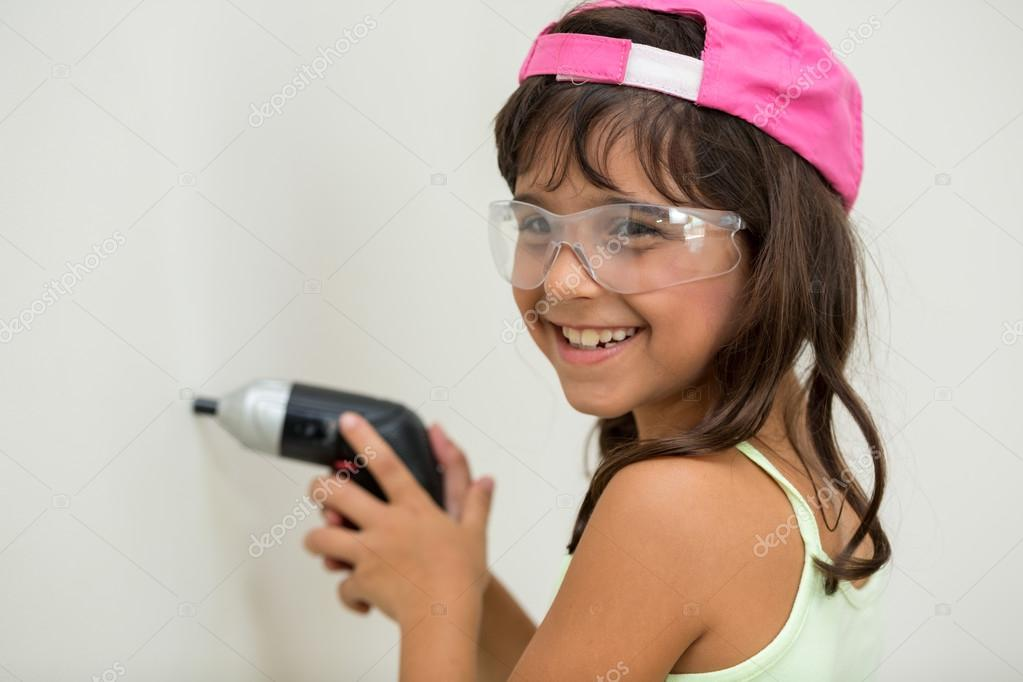 Young girl using screwdriver and cap