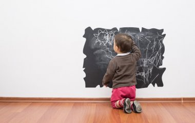 Little baby girl drawing on the wall