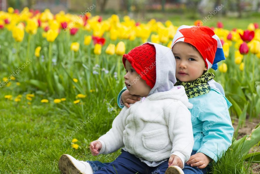 Two little girl with tulips in background