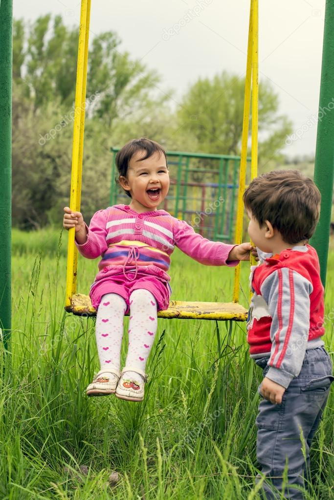 Two little kids having fun on a swing on summer day