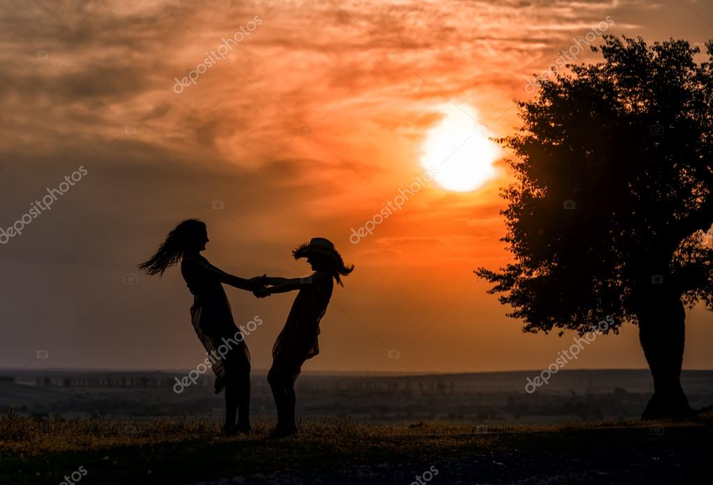 A silhouette of two women dancing on the grass at sunset time