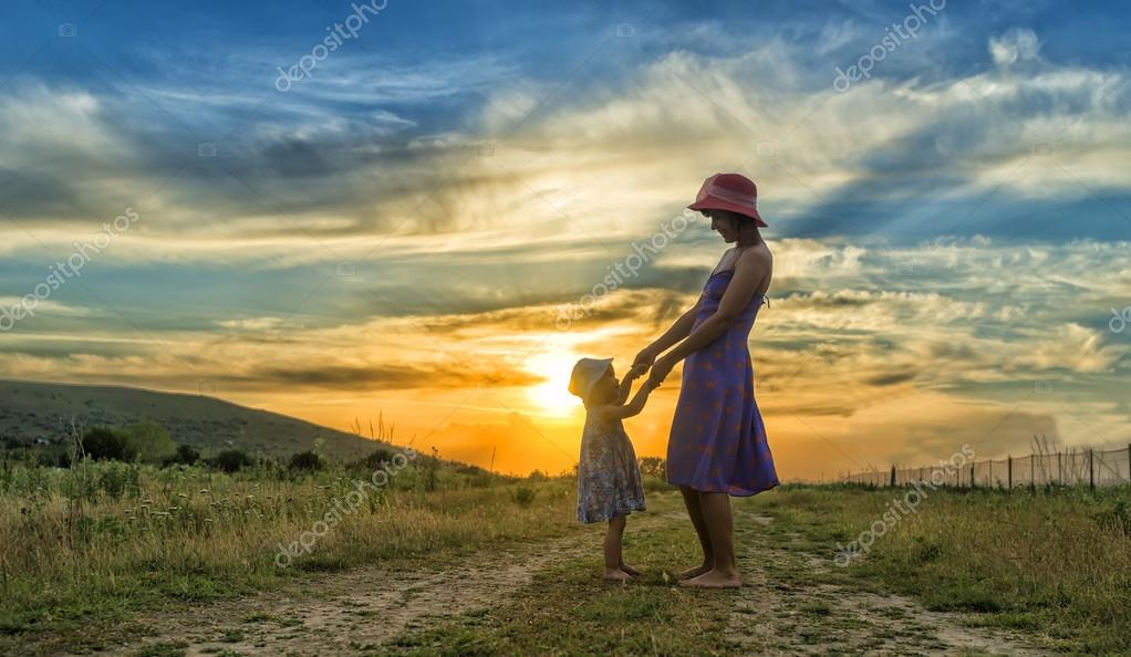 Happy mother and daughter having fun at sunset