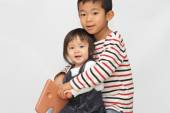 Fotografia Japanese brother and sister playing with rocking horse (6 years old boy and 1 year old girl)