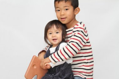 Japanese brother and sister playing with rocking horse (6 years old boy and 1 year old girl)