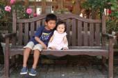 Fotografia Giapponese fratello e sorella (5 anni vecchio ragazzo e ragazza 0 anni) seduto sulla panchina