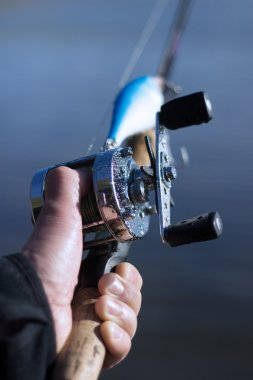 Male hand on a wet round fishing reel