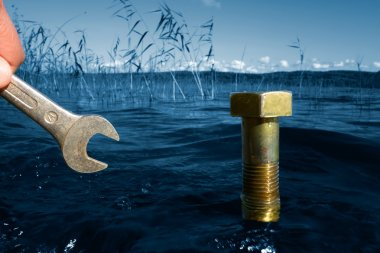 Nature protection concept: Fingers holding tool nearby massive bolt in blue lake water