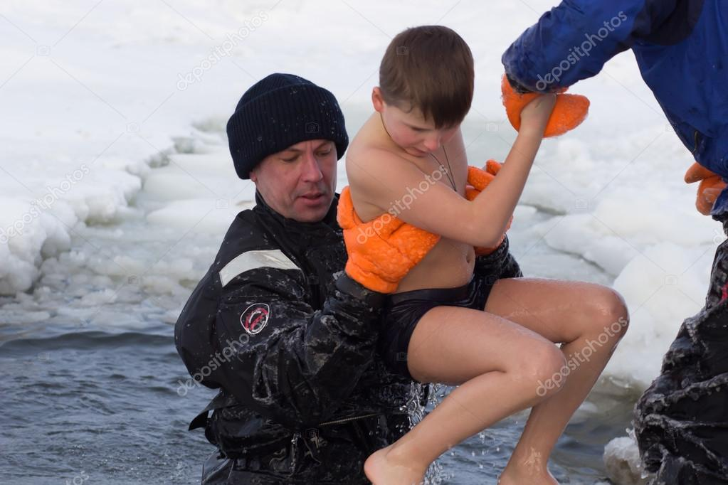 Cherkassy, Ukraine - January 19, 2016: lifeguard rescues a boy pulling it from the ice-cold water