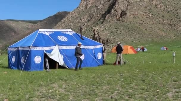 Fly fishing guides standing outside the kitchen tent at a camp at the bottom of a mountain in Mongolia