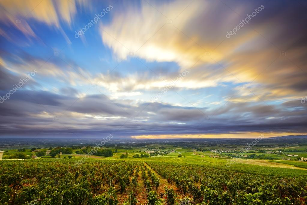 Clouds in long exposure at sunrise time over vineyards of Beaujo