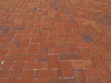 Multi-colored Red brick sidewalk laid in a herringbone pattern.