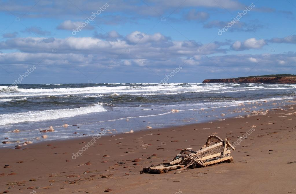 Broken lobster trap on a beach with waves rolling in on Prince Edward Island.