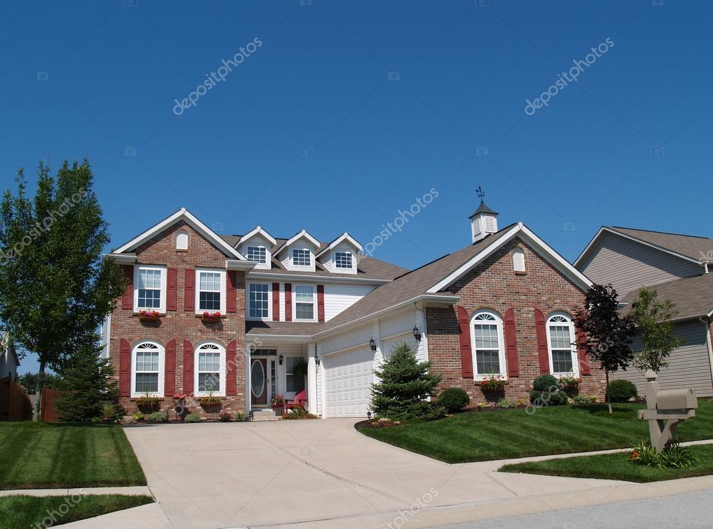 Two Story Brick Residential Home With Red Shutters Window Flower